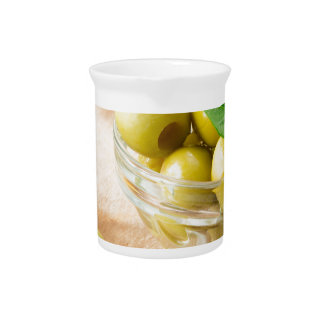 Glass cup with green pitted olives pitcher