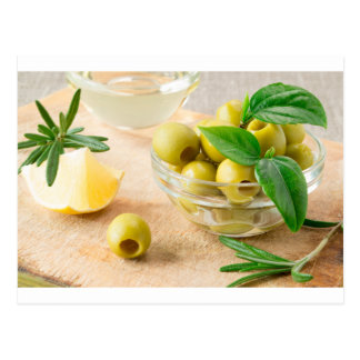 Glass cup with green pitted olives postcard