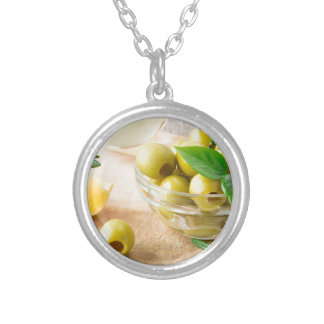 Glass cup with green pitted olives silver plated necklace