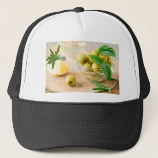 Glass cup with green pitted olives trucker hat