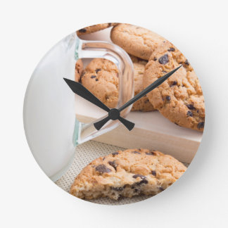 Glass cup with milk and oatmeal cookies clock