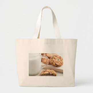 Glass cup with milk and oatmeal cookies large tote bag