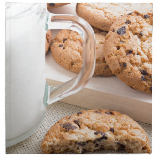 Glass cup with milk and oatmeal cookies napkin