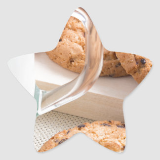 Glass cup with milk and oatmeal cookies star sticker