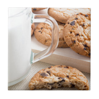 Glass cup with milk and oatmeal cookies tile