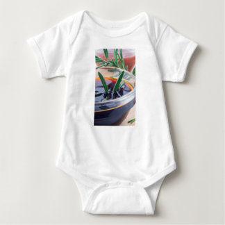 Glass cup with soy sauce and rosemary baby bodysuit