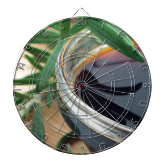 Glass cup with soy sauce and rosemary leaves close dartboard