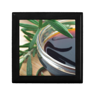 Glass cup with soy sauce and rosemary leaves close gift box