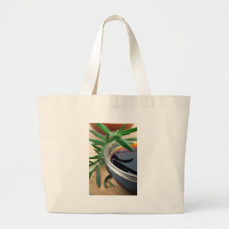 Glass cup with soy sauce and rosemary leaves close large tote bag