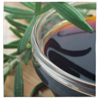 Glass cup with soy sauce and rosemary leaves close napkin
