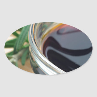 Glass cup with soy sauce and rosemary leaves close oval sticker