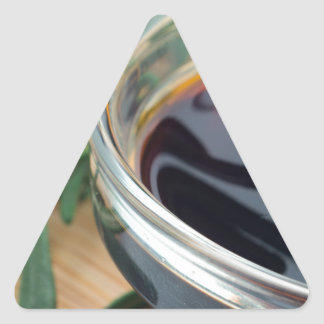 Glass cup with soy sauce and rosemary leaves close triangle sticker