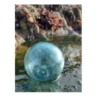 Glass Float on wet sand. Postcard