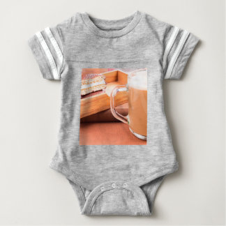 Glass mug with hot chocolate and biscuits baby bodysuit