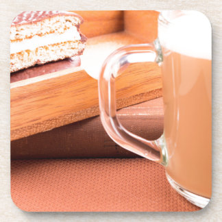 Glass mug with hot chocolate and biscuits coaster
