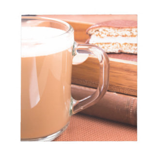 Glass mug with hot chocolate and biscuits notepad