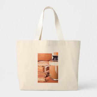 Glass mug with hot chocolate on a table large tote bag
