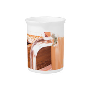 Glass mug with hot chocolate on a table pitcher