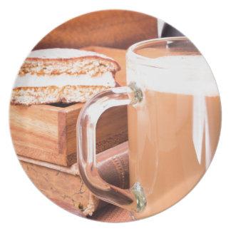Glass mug with hot chocolate on a table plates