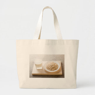 Glass of milk and a plate of cereal closeup large tote bag