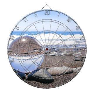 Glass sphere on stones at beach and coast dart boards