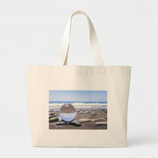Glass sphere on stones at beach and coast large tote bag