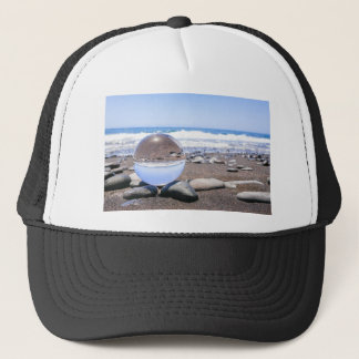 Glass sphere on stones at beach and coast trucker hat
