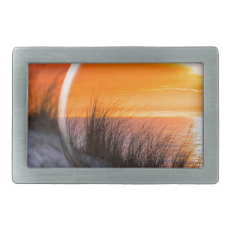 Glass sphere reflecting orange sunset belt buckle