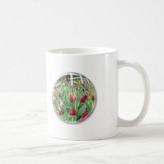 Glass sphere reflecting red tulips flower coffee mug