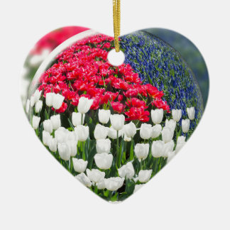 Glass sphere reflecting red white tulips and blue ceramic heart ornament