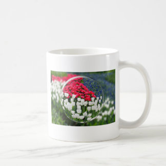 Glass sphere reflecting red white tulips and blue coffee mug