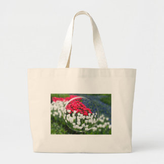 Glass sphere reflecting red white tulips and blue large tote bag