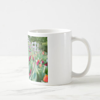 Glass sphere reflecting tulips flowers coffee mug