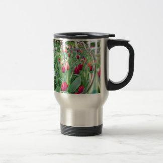 Glass sphere reflecting tulips flowers travel mug