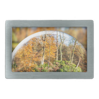 Glass sphere with autumn nature reflection in it belt buckle