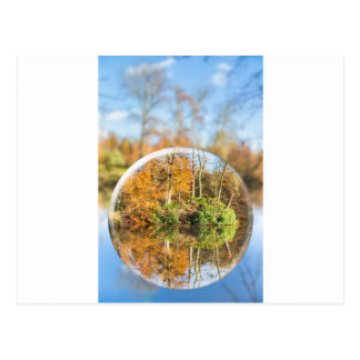 Glass sphere with autumn nature reflection in it postcard
