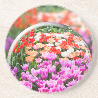 Glass sphere with various tulips in flowers field. beverage coasters