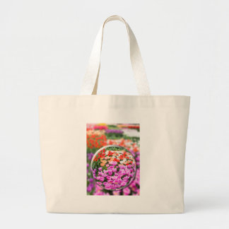 Glass sphere with various tulips in flowers field. large tote bag