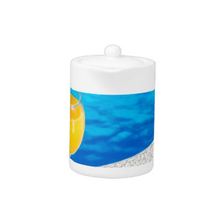 Glass with orange juice on edge of swimming pool