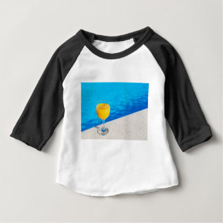 Glass with orange juice on edge of swimming pool baby T-Shirt