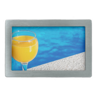 Glass with orange juice on edge of swimming pool belt buckles