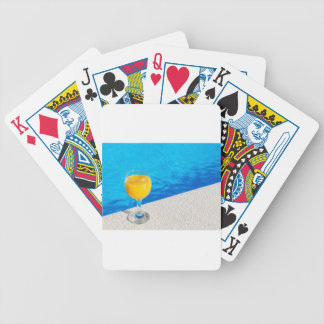 Glass with orange juice on edge of swimming pool bicycle playing cards