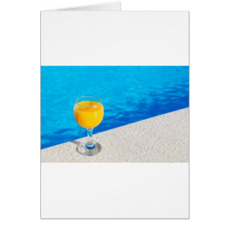 Glass with orange juice on edge of swimming pool card
