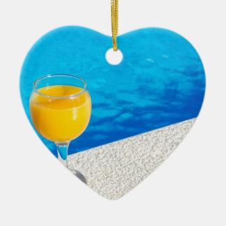 Glass with orange juice on edge of swimming pool ceramic heart ornament