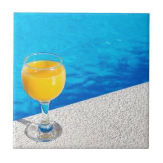 Glass with orange juice on edge of swimming pool ceramic tile