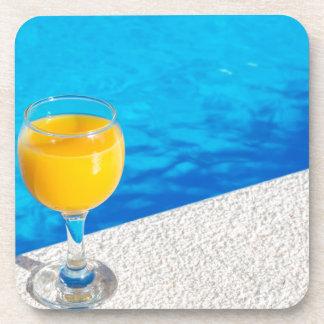 Glass with orange juice on edge of swimming pool coasters