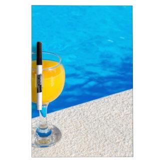 Glass with orange juice on edge of swimming pool dry erase board