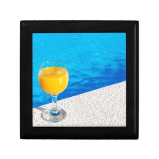 Glass with orange juice on edge of swimming pool gift box