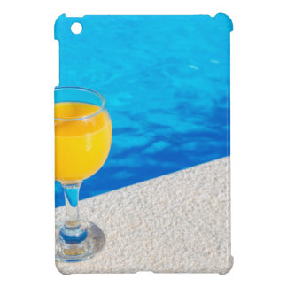 Glass with orange juice on edge of swimming pool iPad mini cases