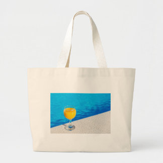 Glass with orange juice on edge of swimming pool large tote bag